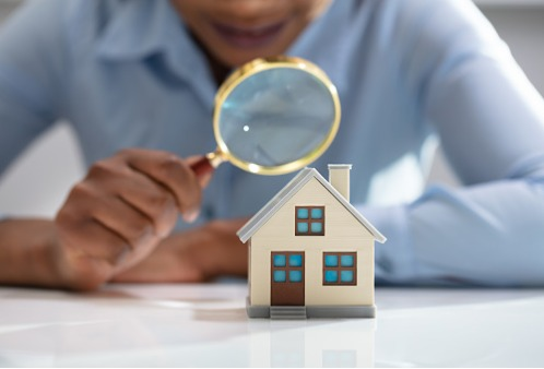 An individual with a magnifying glass examining a small home, representing a Public Adjuster