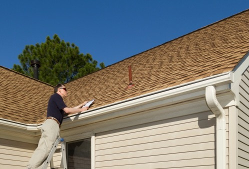 A public adjuster examining a roof for any damage