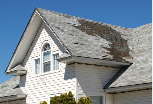 A roof with missing shingles after a storm, needing Storm Damage Repair